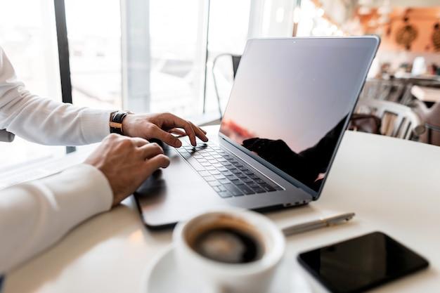 전문적인 성공적인 비즈니스 남자는 근무일에 밝은 사무실에 앉아 노트북에서 작동