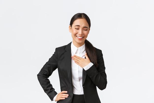 Профессиональная успешная деловая женщина в черном костюме разговаривает, смеется и трогает грудь, как ей что-то смешное или лестное, хвалят за хорошую работу на работе, белый фон