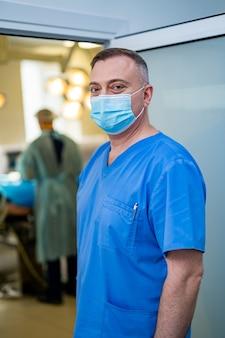 Профессиональный хирург. серьезный мужчина в медицинской форме и маске, стоящий в операционной. работа в больнице
