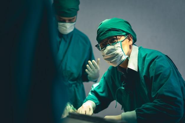 Бригада профессиональных хирургических врачей, оперирующих пациента в операционной в больнице