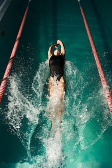 Professional swimmer swimming on back