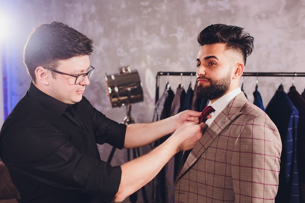 Professional tailor taking measurements for sewing suit at tailors shop