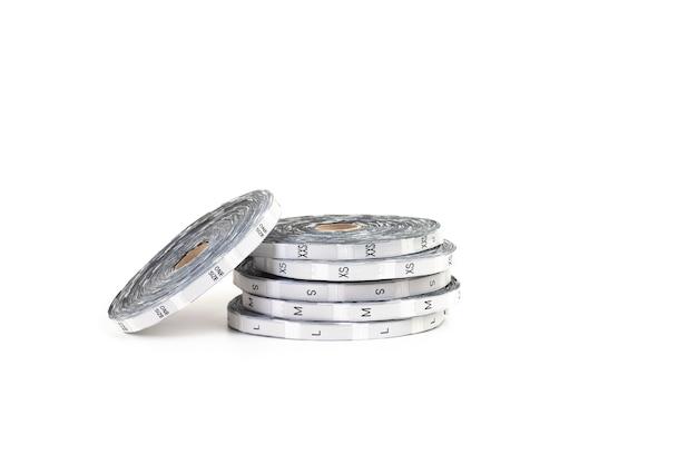 Профессиональное пошивочное оборудование в виде серебряных катушек с размерными бирками и надписью размеров из ...