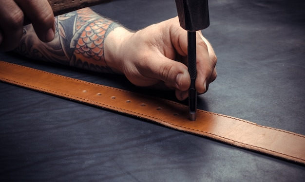 Профессиональный кожевник, вырезающий формы из кожи для нового продукта на полке