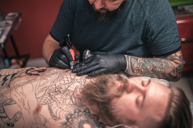 Professional tattoo artist does tattoo on the skin of his client in studio.