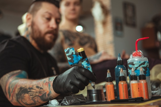 Professional tattoo artist doing a new tattoo for his client