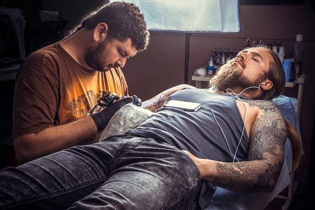 タトゥースタジオでタトゥーをしているプロのタトゥーアーティスト。