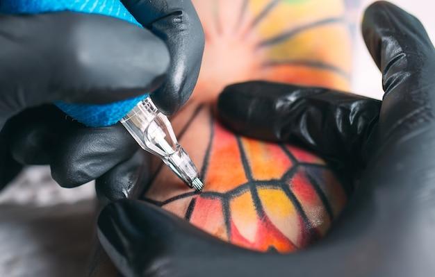 Профессиональный татуировщик делает татуировку на руке молодой девушки.
