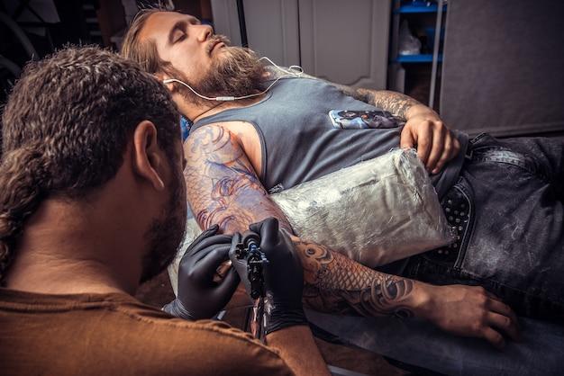 문신 스튜디오에서 문신을 만드는 과정을 보여주는 전문 문신 아티스트. / 문신 스튜디오에서 직장에서 전문 문신가.