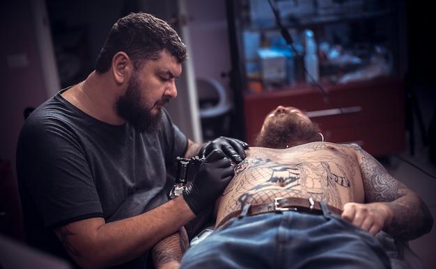 전문 문신 예술가는 문신 가게에 문신을하는 과정을 보여줍니다.