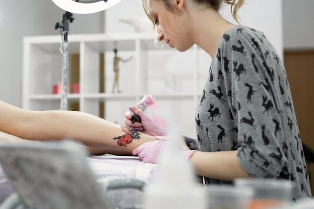 젊은 여성의 다리에 문신을 만드는 전문 문신 아티스트