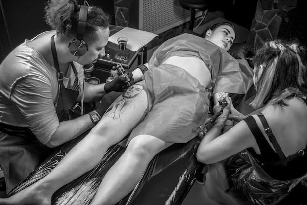 Профессиональный татуировщик демонстрирует процесс нанесения татуировки в тату студии