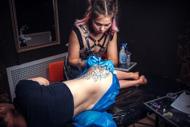 전문 문신가는 그의 살롱에서 문신을합니다.