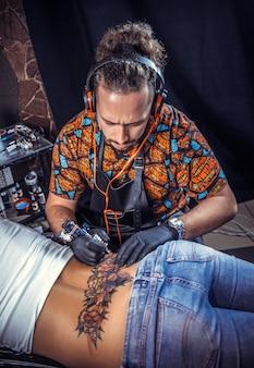 Профессиональный татуировщик делает татуировку на коже своего клиента