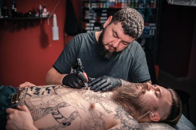 Профессиональный татуировщик делает рисунки тату в мастерской студии.