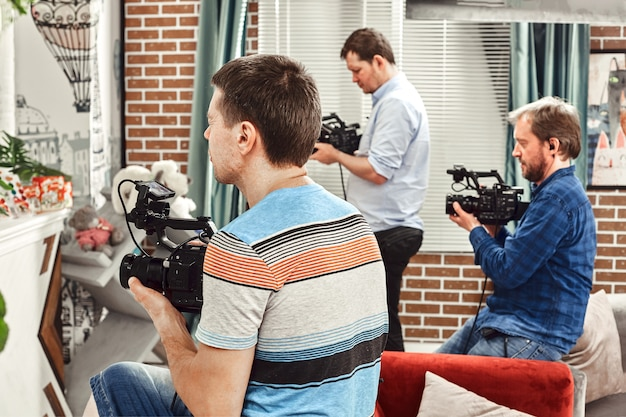 Professional team of cameramen with a director filming commercial ads