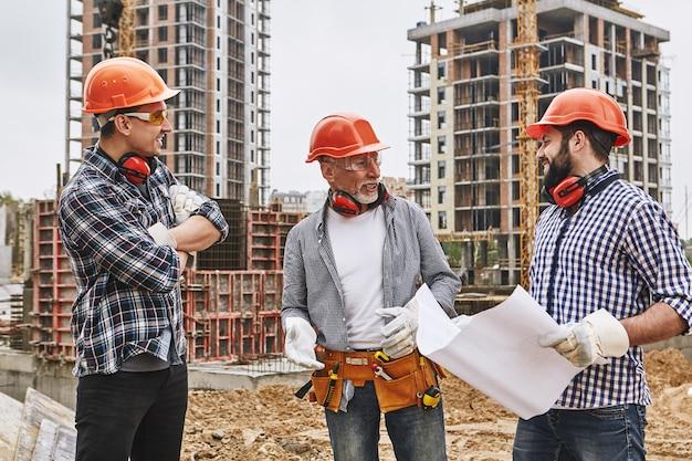 보호복과 빨간 헬멧을 쓴 전문 건설팀 그룹이 새로운 프로젝트에 대해 논의하고 있습니다