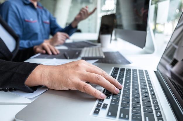 Itオフィスのソフトウェア開発コンピューターでプロジェクトに取り組んでいるプログラマーの専門家チーム
