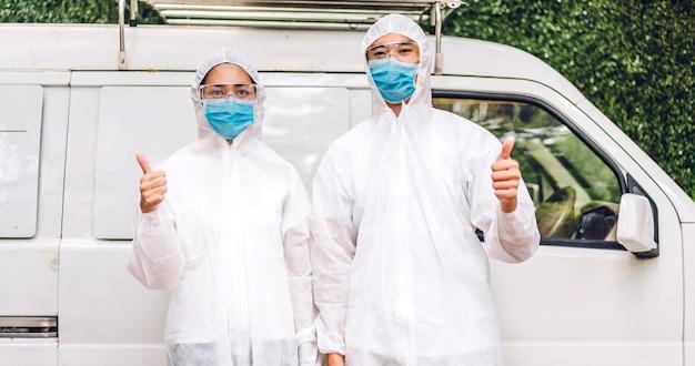 防護マスクと白いスーツ消毒剤スプレークリーニングウイルスの消毒作業員の専門チーム