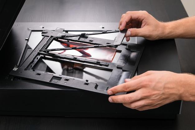 ネガフィルムとスライドを手でスキャンする専門技術者