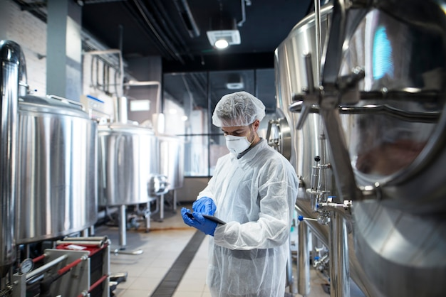 生産性と品質をチェックする生産工場でタブレットを使用する専門の技術者