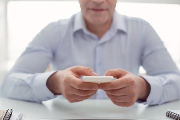 専門技術。テーブルに座っている間素敵なハンサムな男の手にある現代のスマートフォンの選択的な焦点