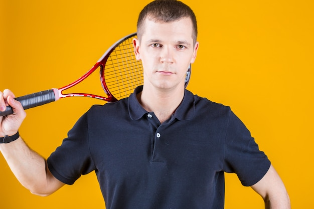 Professional tennis player man on a bright yellow wall