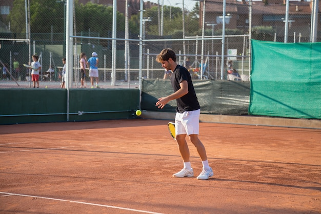 Professional tennis player playing tennis on a clay tennis court on a sunny day.