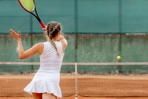 화창한 날에 클레이 테니스 코트에서 테니스를하는 프로 테니스 선수