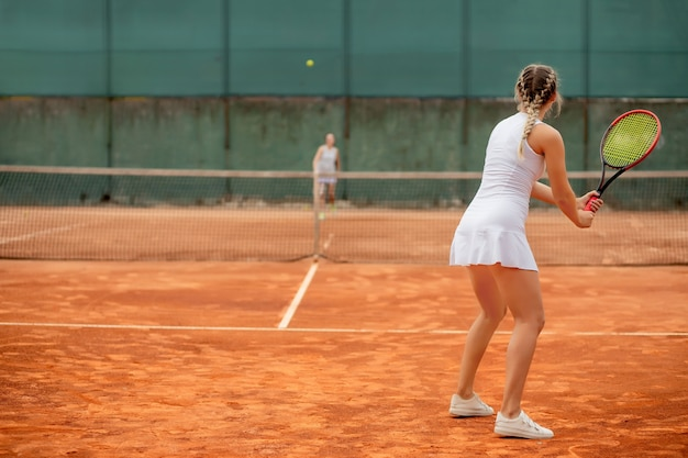 粘土のテニスコートでテニスをしているプロのテニスプレーヤー