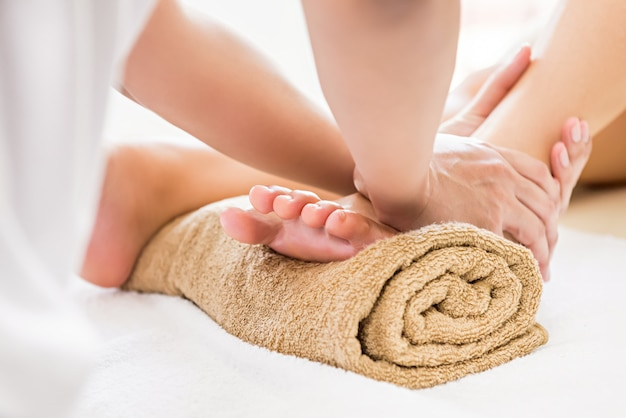 Professional therapist giving reflexology foot massage to a woman in spa