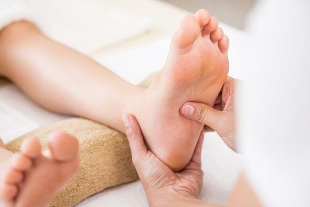 Professional therapist giving reflexology thai foot massage to a woman in spa