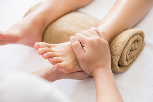 Professional therapist giving relaxing reflexology thai foot massage to a woman in spa