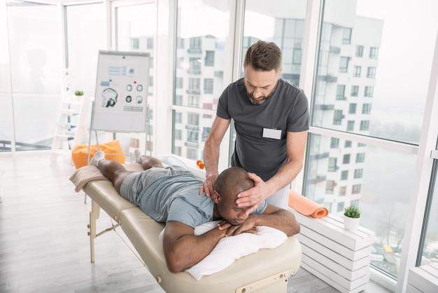 Профессиональный терапевт. умный опытный мужчина держит голову пациента, работая терапевтом в реабилитационном центре