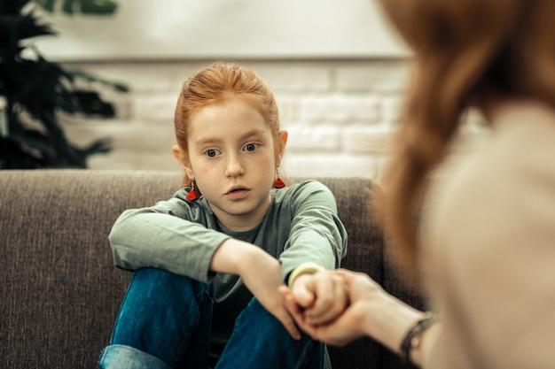 専門的な治療。ソファに座って医者に手を差し伸べるかわいい楽しい女の子