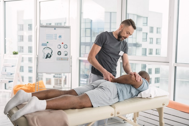 Professional therapy. smart professional therapist using a special technique while doing massage for his patient