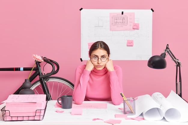 スケッチの作成に取り組んでいるプロの疲れた女性建築家は、長時間の作業にうんざりしていると感じています。グラフィックの支出は、紙のステッカーで囲まれたデスクトップでポーズを計画するアイデアを改善しようとしています