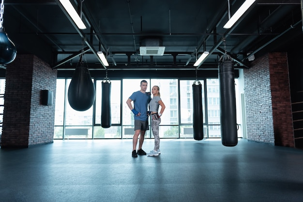 Professional trainers. two professional fitness trainers standing in spacious gym near big window with city view