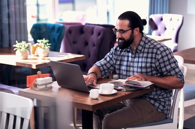 Professional translator. professional remote translator feeling busy translating documents using his laptop