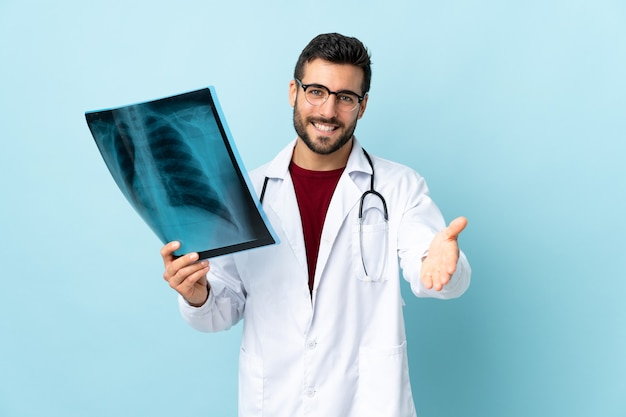 Professional traumatologist holding radiography isolated on blue handshaking after good deal