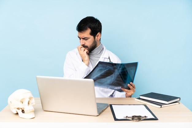 Профессиональный травматолог на рабочем месте, сомневаясь