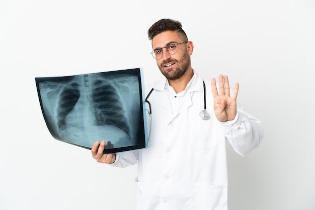 Профессиональный травматолог изолирован на белой стене счастливым и считает четыре пальцами