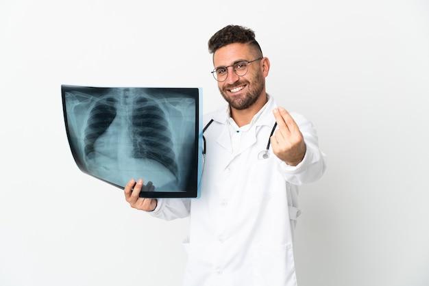 Профессиональный травматолог изолирован на белой стене, делая денежный жест