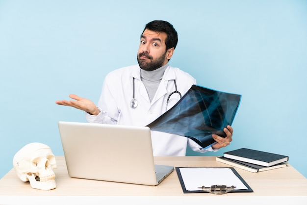 Professional traumatologist in workplace having doubts while raising hands