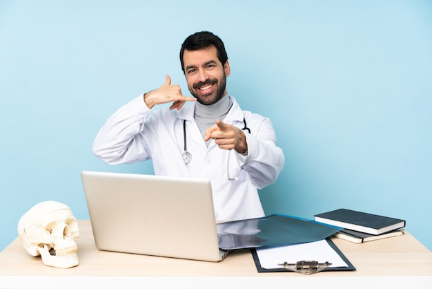 Professional traumatologist in workplace making phone gesture and pointing front