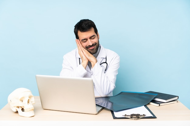 Professional traumatologist in workplace making sleep gesture in dorable expression