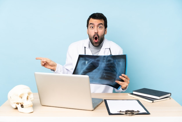 Professional traumatologist in workplace surprised and pointing finger to the side