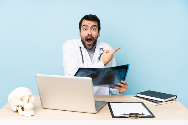 Professional traumatologist in workplace surprised and pointing side