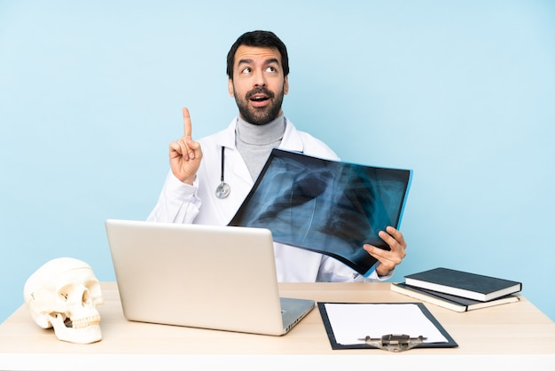 Professional traumatologist in workplace thinking an idea pointing the finger up