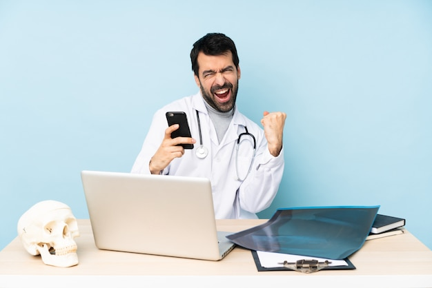 Professional traumatologist in workplace with phone in victory position